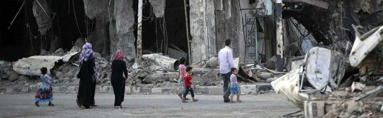 Syrians walking amid rubble in Deir ez-Zor (Reuters)
