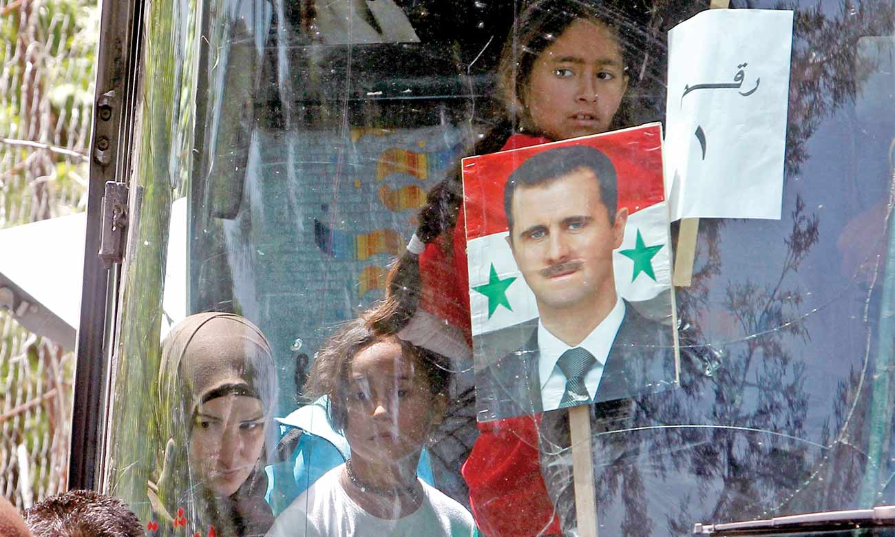 Syrian President Bashar al-Assad's photo on a bus taking Syrian refugees  back to Syria - Lebanon on April 18, 2018 (Reuters)