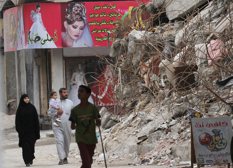 Residents walking through demolished buildings in Raqqa - October 12, 2018 (Reuters)