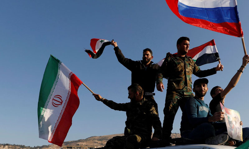 Troops raising Russian and Iranian flags, condemning the U.S. attacks on Syria – April 2018 (Reuters)