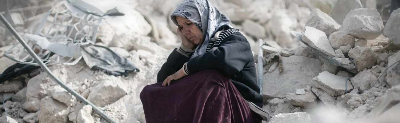 Syrian woman sits among rubble in Aleppo - 2013 (AFP)