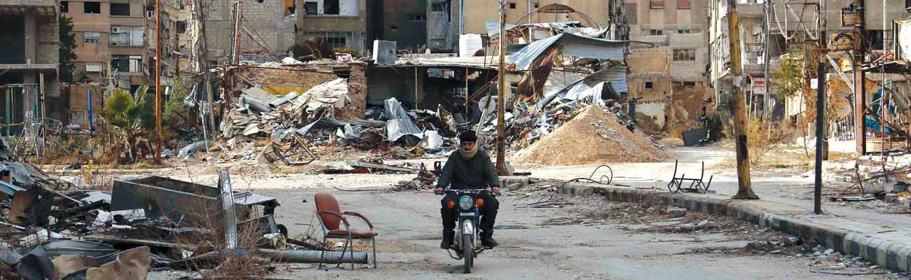 A man riding his motorcycle through the wrecked buildings in Harasta, East of Damascus. (AFP)