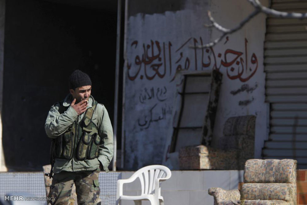 Pro-Syrian regime forces officer smoking a cigarette in the town of Rabia - January 2017 - Reuters