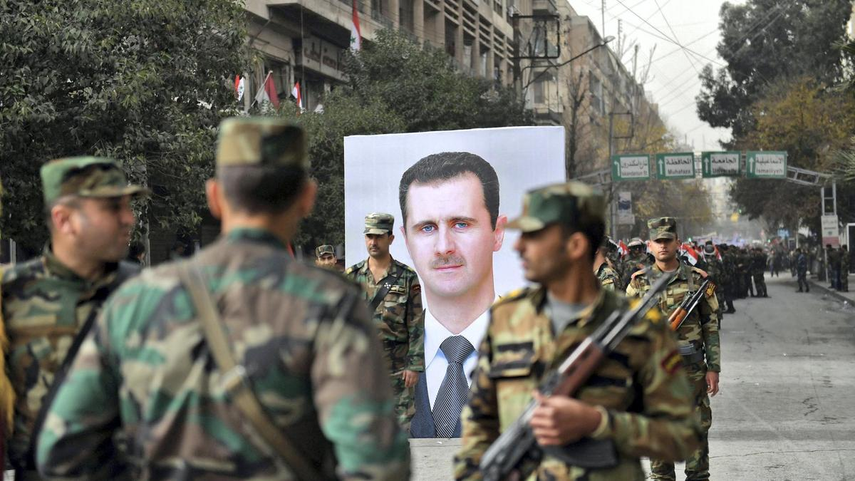 Syrian soldiers passing in front of Syrian President Bashar al-Assad's photo which marks the anniversary of his forces' control over the city of Aleppo- December 21, 2017 (AFP)