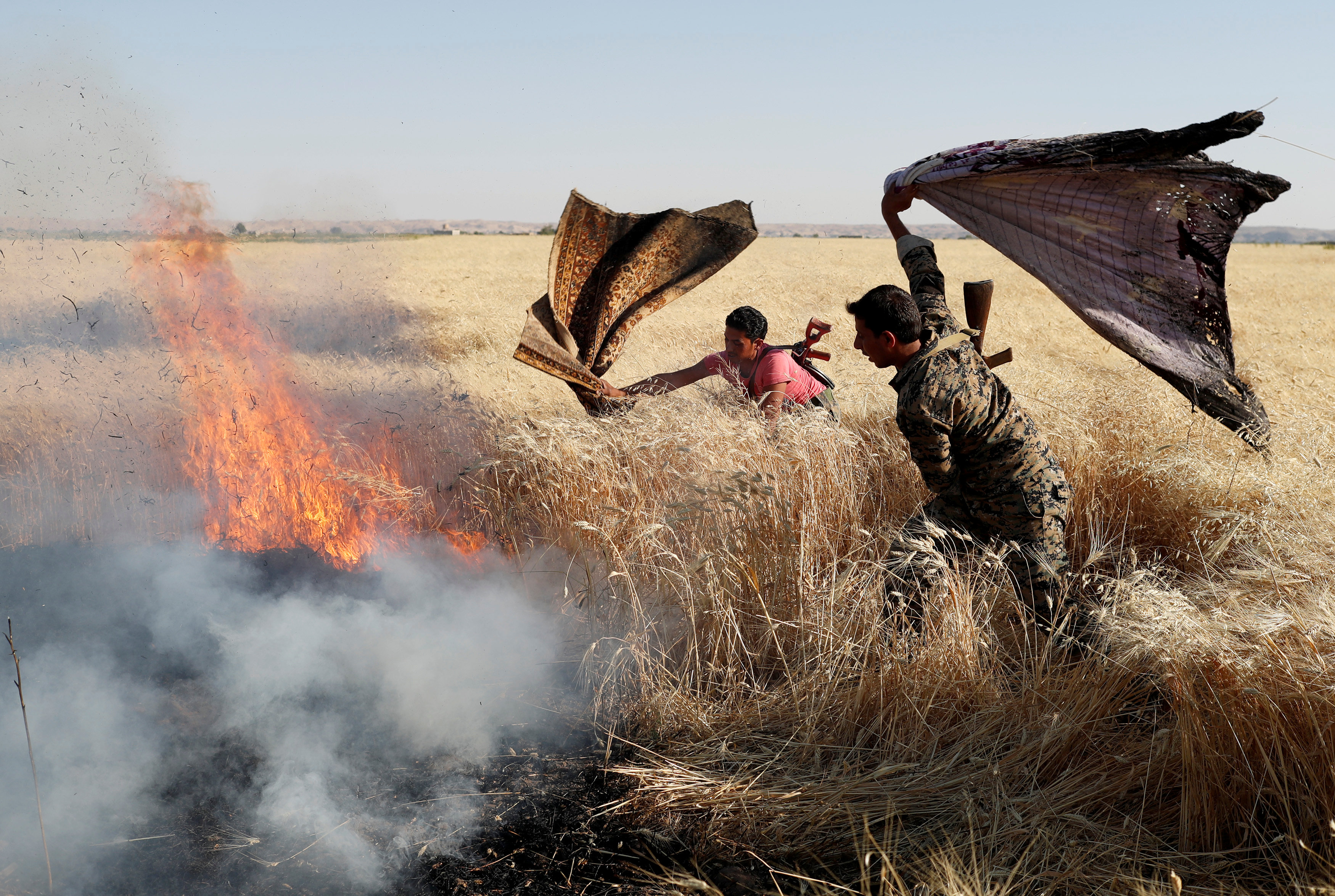 Kurdish fighters extinguishing fire in a wheat field after clashes with ISIS - December 1, 2017 (Reuters)