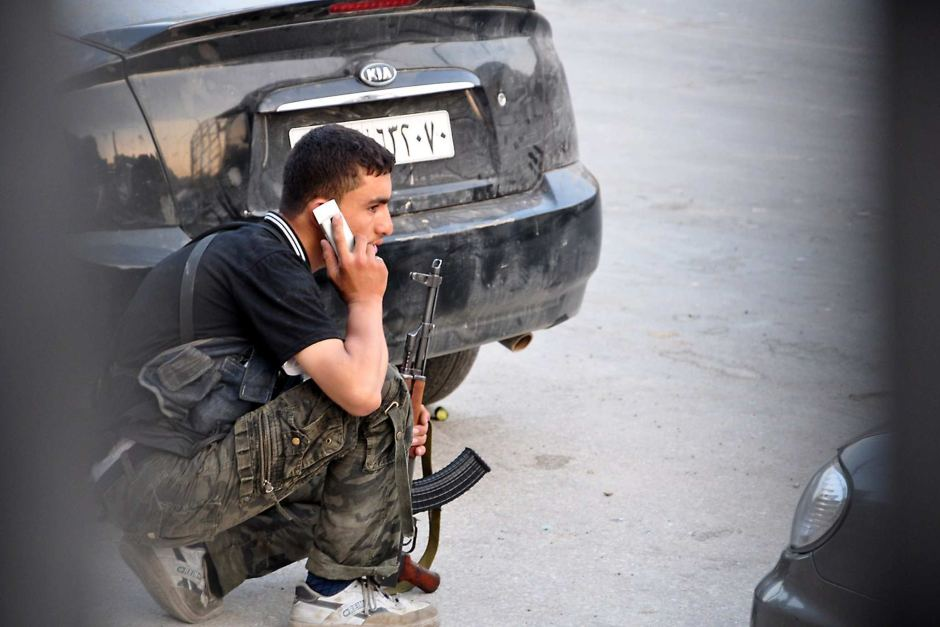 A fighter affiliated to the Syrian opposition during clashes with police in Salihin neighborhood in Aleppo – July 31, 2012 (AFP)