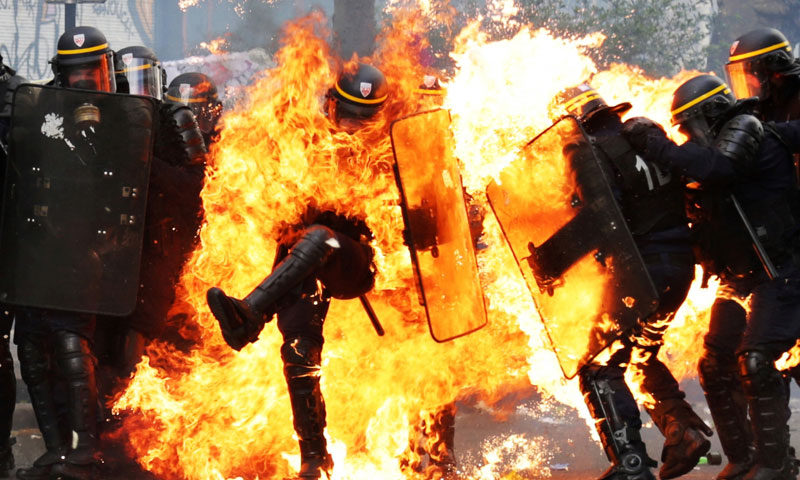 An officer catching fire during the 2017 May Day protests (AFP)