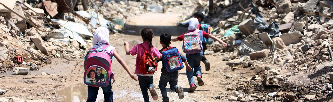 School students running across a street to their school in Eastern Ghouta - May 2016 (AFP)