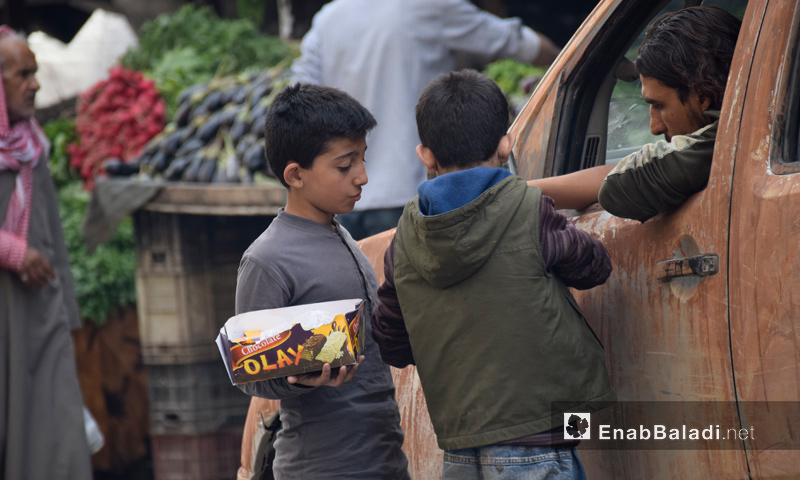 Two children selling biscuits to passers-by in the city of Aleppo - October 2016 (Enab Baladi)