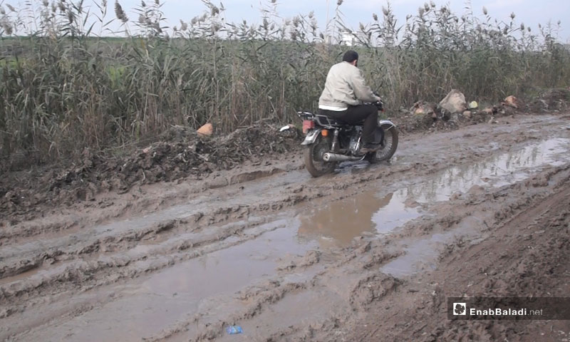 A man driving a motorcycle in the mud in the Bab al-Taqa village, rural Hama – December 22, 2018 (Enab Baladi)
