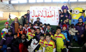 """""""I Have the Right to Play"""" event in the city of Idlib (the sign says: Children Not Workers) – January 18, 2019 (Enab Baladi)"""