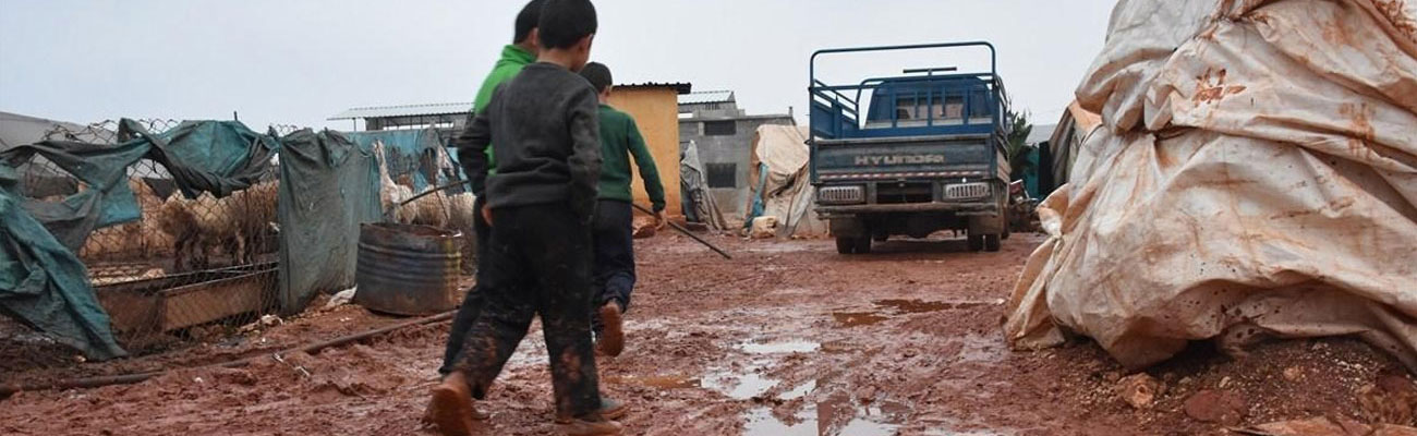 Children walking through mud amid the storm that hit northern Syrian camps - 2018 (AFP)