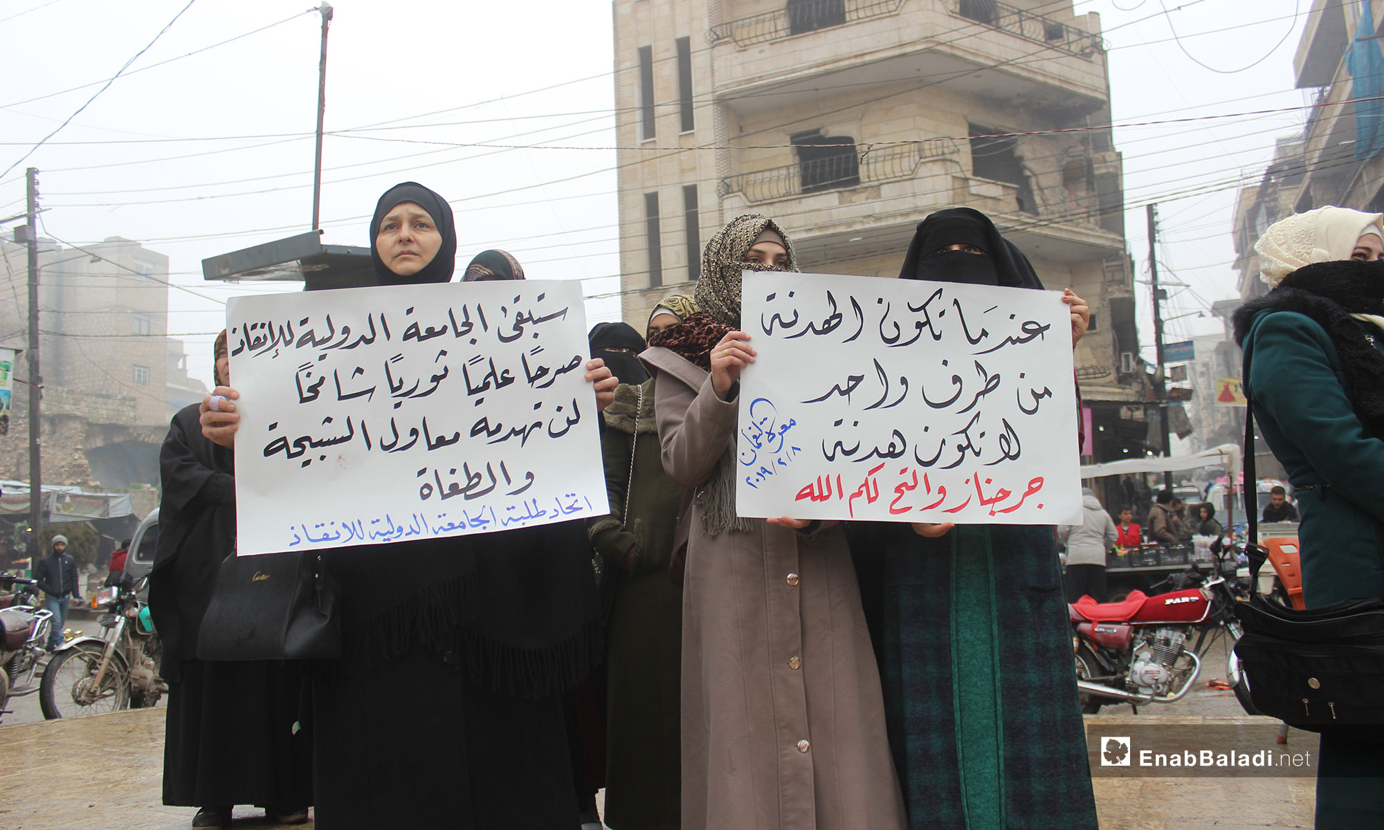A demonstration in the city of Maarrat al-Nu'man protesting the decision of closing the International Rescue university in Idlib [From left to right the signs say: The International Rescue University will Remain an lofty Educational and Rebellious Edifice, which Tools of Thugs and Tyrants Would not Dare Destroy (Students Union of the International Rescue University). A One-side truce is Not a Truce (Jarjanaz and al-Tah, God Is There for You!)]– February 8, 2019 (Enab Baladi)
