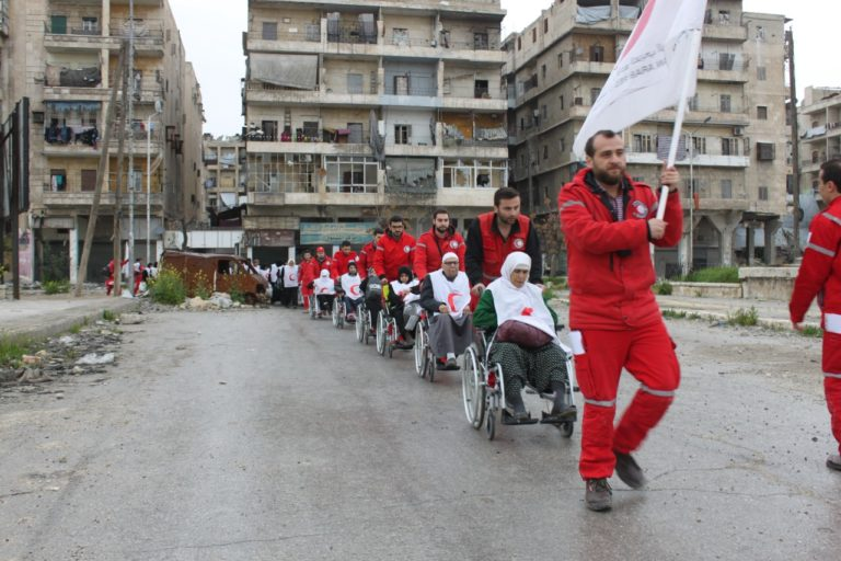 The volunteers of the Syrian Arab Red Crescent in Aleppo transporting the people in need for medical assistance via the front lines - 2017 (Red Crescent)