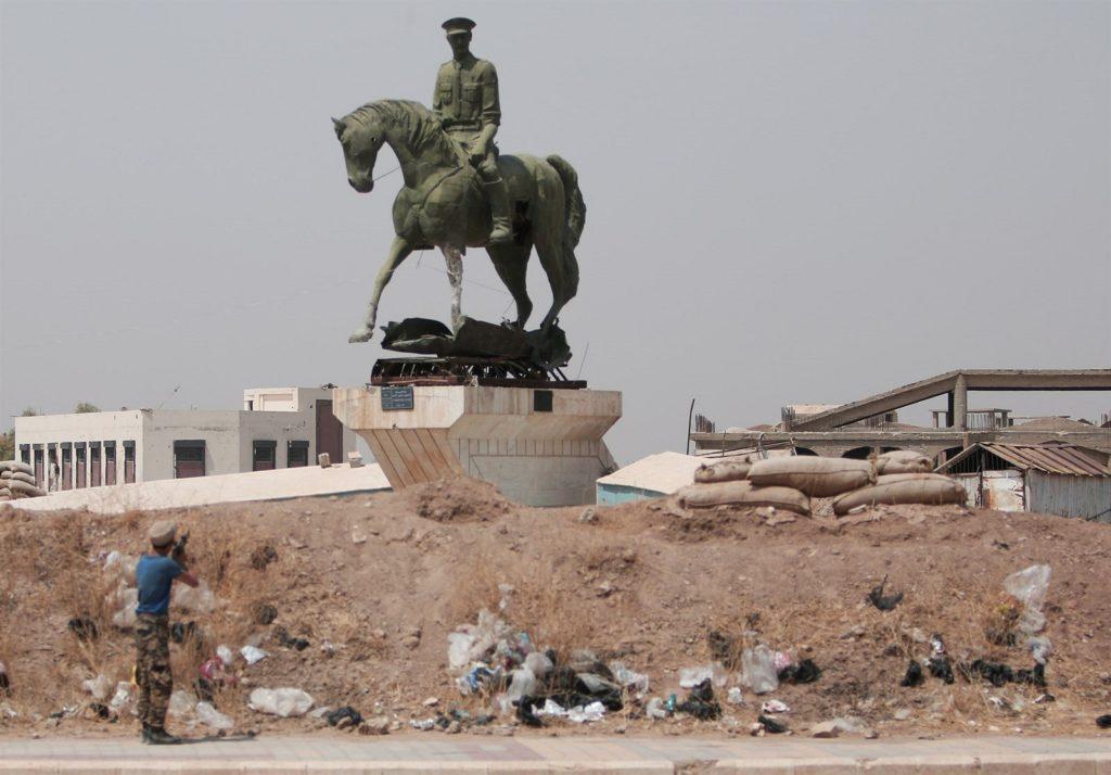 Kurdish fighter shoots Bassel al-Assad's statue in al-Hasakah - May 2017 (Reuters)