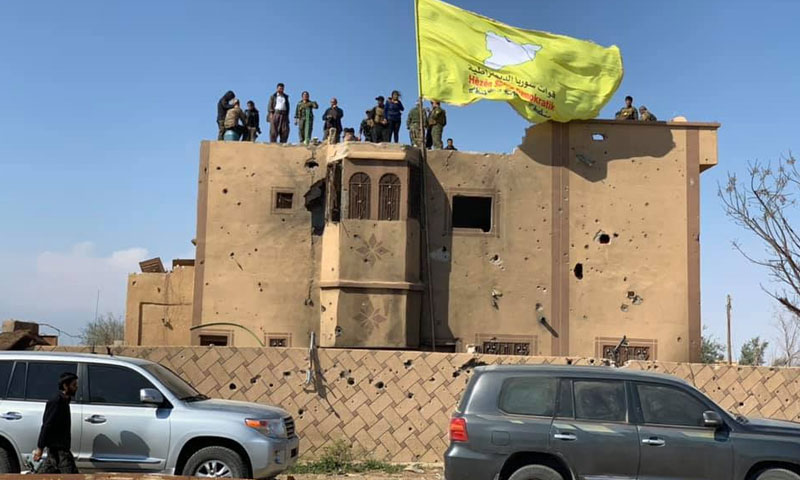 """The flag of the """"Syrian Democratic Forces"""" raised in the last strongholds of the """"Islamic State"""" in al-Baghuz, east of the Euphrates – March 23, 2019 (Photographer Mohammed Hassan)"""