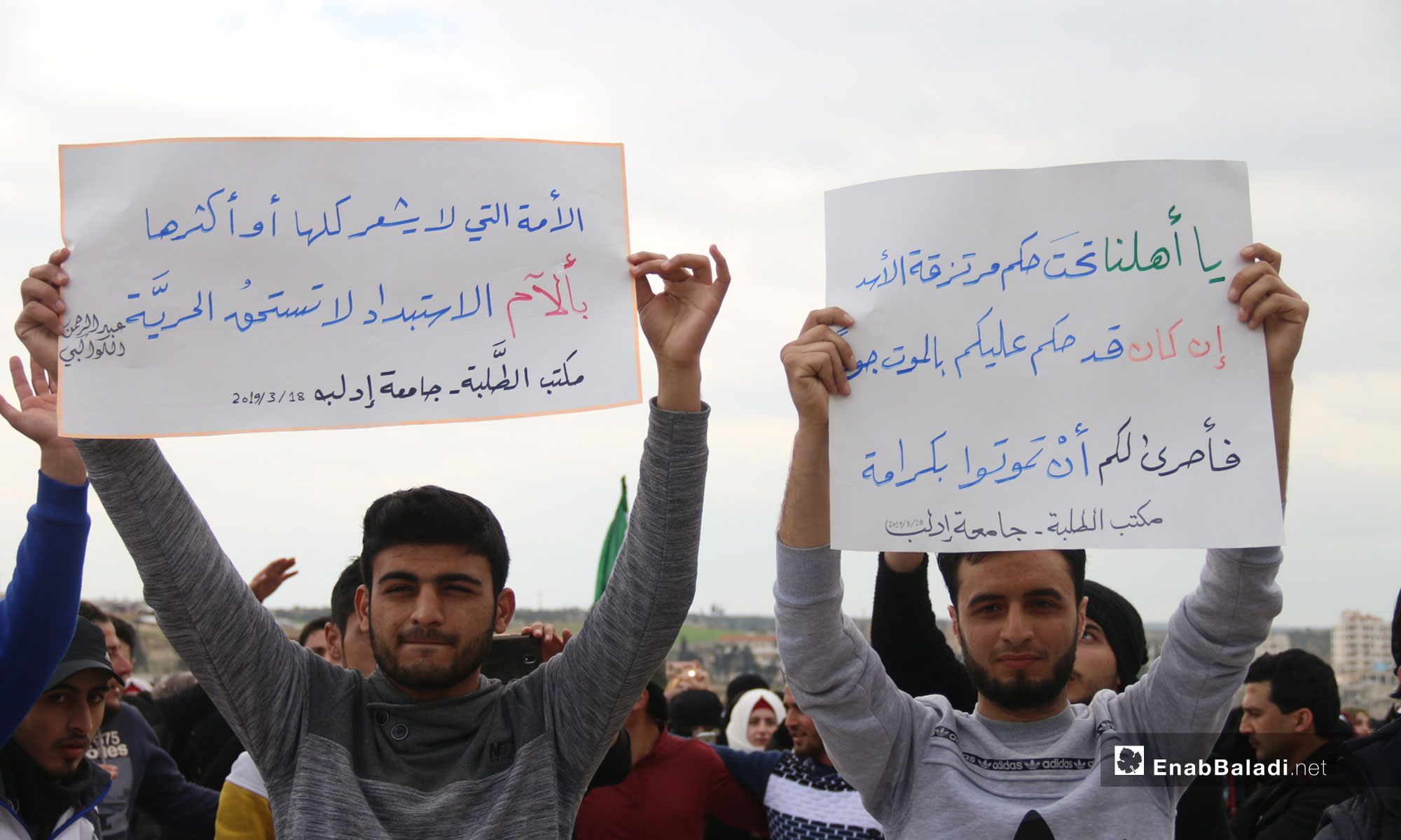 """A demonstration by Idlib University students on the Syrian revolution's eighth anniversary. The signs say:  To our people under the power of Assad's mercenaries-If you are sentenced to die of starvation-It is better that you die in dignity- Students Office, Idlib University/ """"A nation, whose part and whole, does not feel the suffering of oppression is not worthy of freedom"""" Abd al-Rahman al-Kawakibi - Students Office, Idlib University  – March 18, 2019 (Enab Baladi)"""