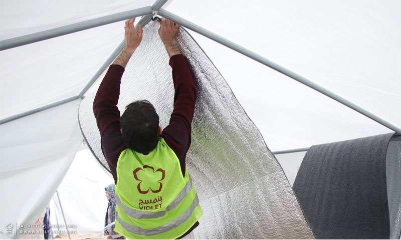 A member of Violet Organization insulating a tent's interior (Facebook)
