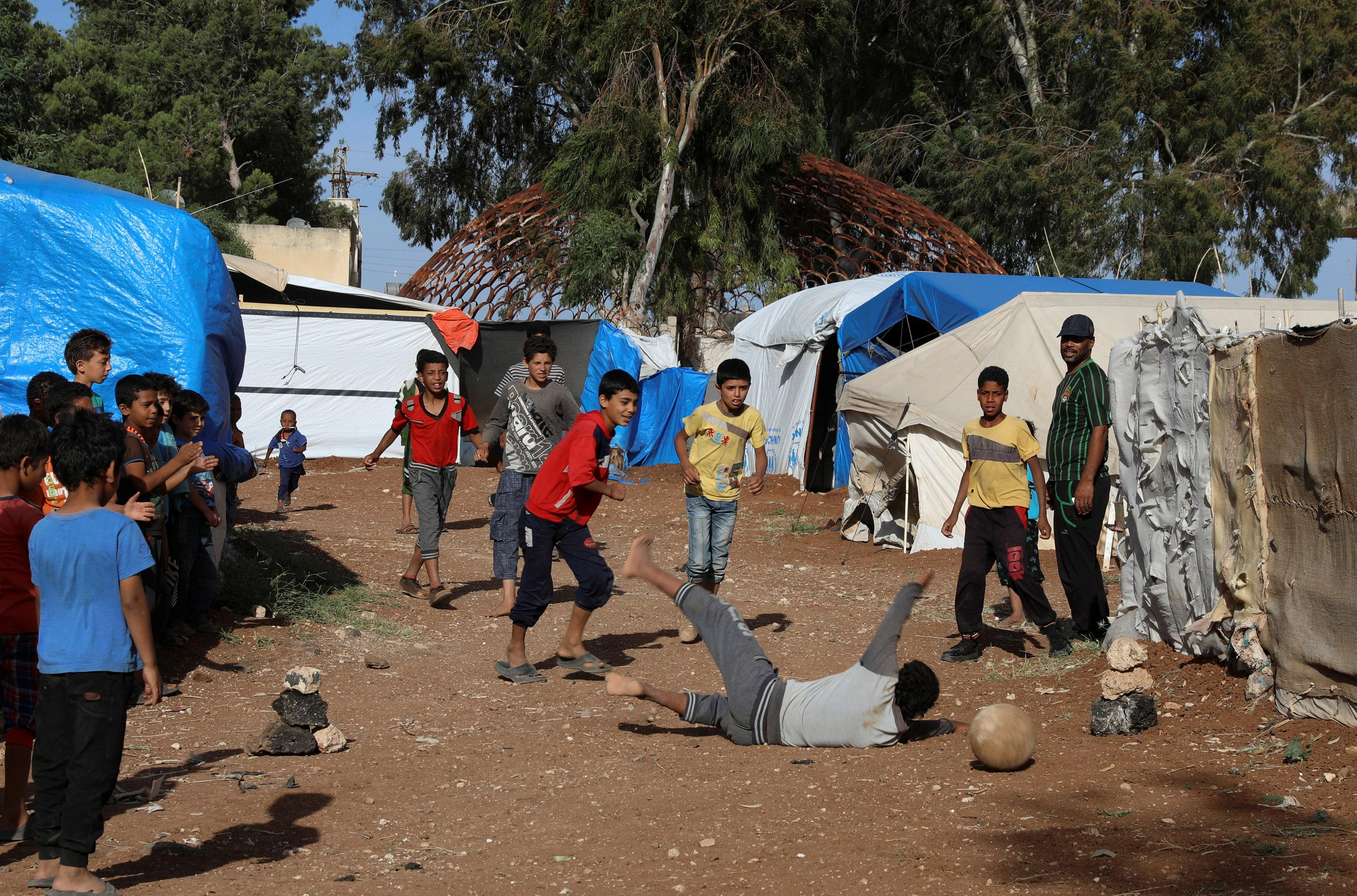 Children playing football in Zayzun refugee camp in Daraa - May 23, 2018 (Reuters)
