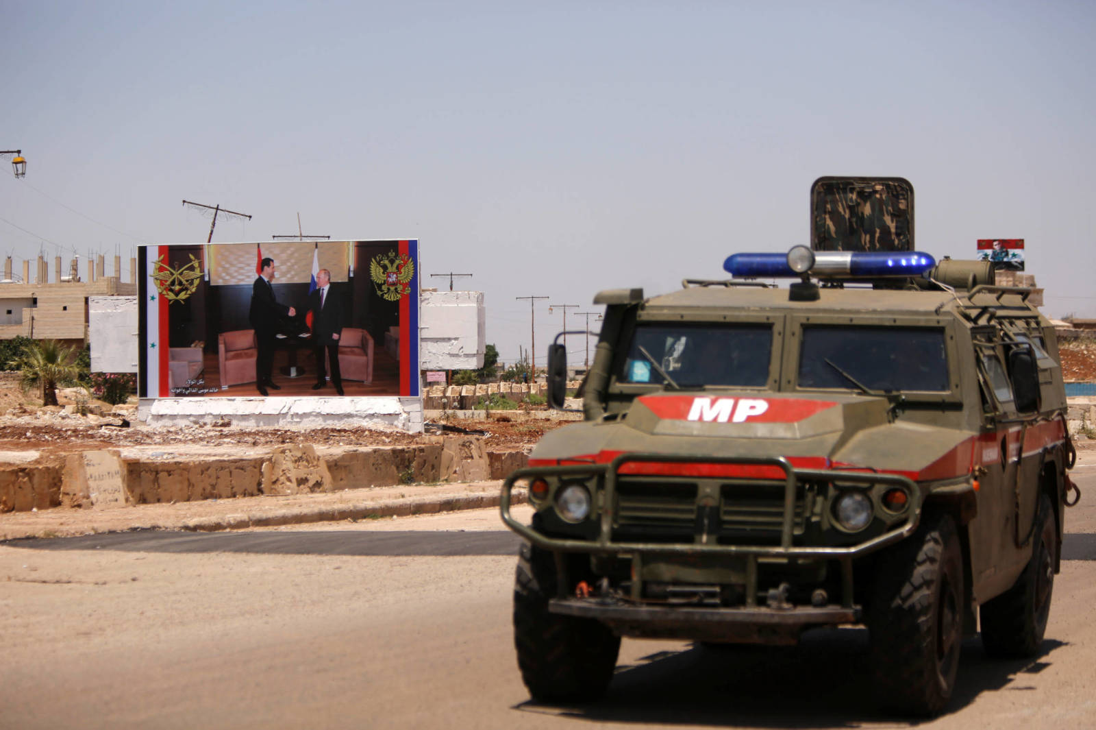 Russian military vehicle near poster of Bashar al-Assad and Putin in Aleppo - June 2018 (Reuters)
