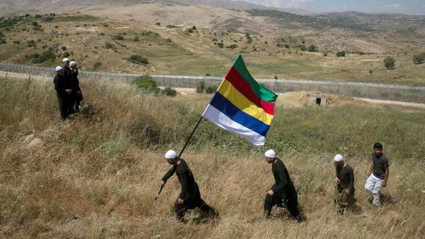 Militants of the united Druze community in the Golan Heights walking near the border fence with Syria - February 2018 (Reuters)
