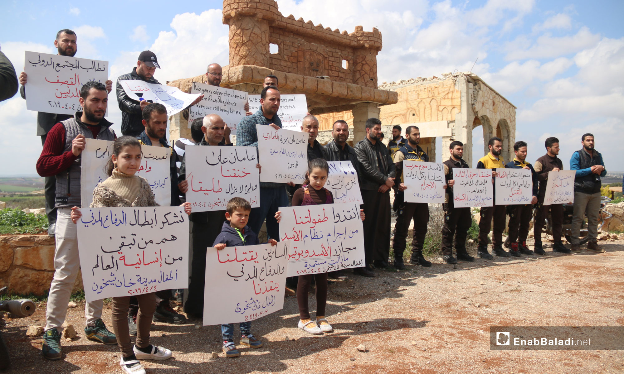 "A vigil at the second anniversary of the chemical massacre of Khan Shaykhun, rural Idlib – April 4, 2019 (Enab Baladi) The signs held by the people say: ""Suffocated, burnt and mutilated, are there any death methods left that you have not tried yet; hold al-Assad accountable, chemical weapons  Khan Shaykhun/ Al-Assad is a war criminal, killing us with all the tools of crime/ two years ago, he suffocated us, and he is yet killing us/ 04.04.2017 is a day that our generations will not forget/ Bashar al-Assad is killing his people with an international license/ Two years have passed since the chemical weapons' massacre and the massacres of the Russians and the regime are yet going on/We demand that the international community stop the shelling and protect the civilians/ Save our childhood from the criminality of the al-Assad regime; Massacres by al-Assad and Putin are continuing/ Two years have passed since we were suffocated and the criminal is still free/The tools are many and the criminal is but one; chemical weapons, aircraft, missiles, and the massacres are still going on/We thank the heroes of the Civil Defense, they are what is left of the world's humanity, the children of the city of Khan Shaykhun/He is making an art out of killing his people and has a plan to get back Golan/Two years have passed since our suffocation, and our children are still suffering the bitterness of daily shelling."""