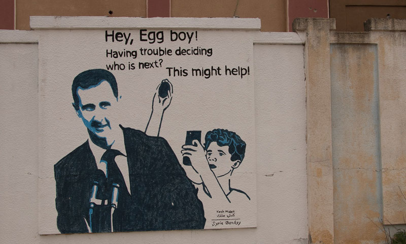 A graffiti on a wall in Idlib, featuring the Australian boy, Will Connolly, egging Bashar al-Assad, the head of the Syrian regime- March 29, 2019 (Kesh Malek Facebook)
