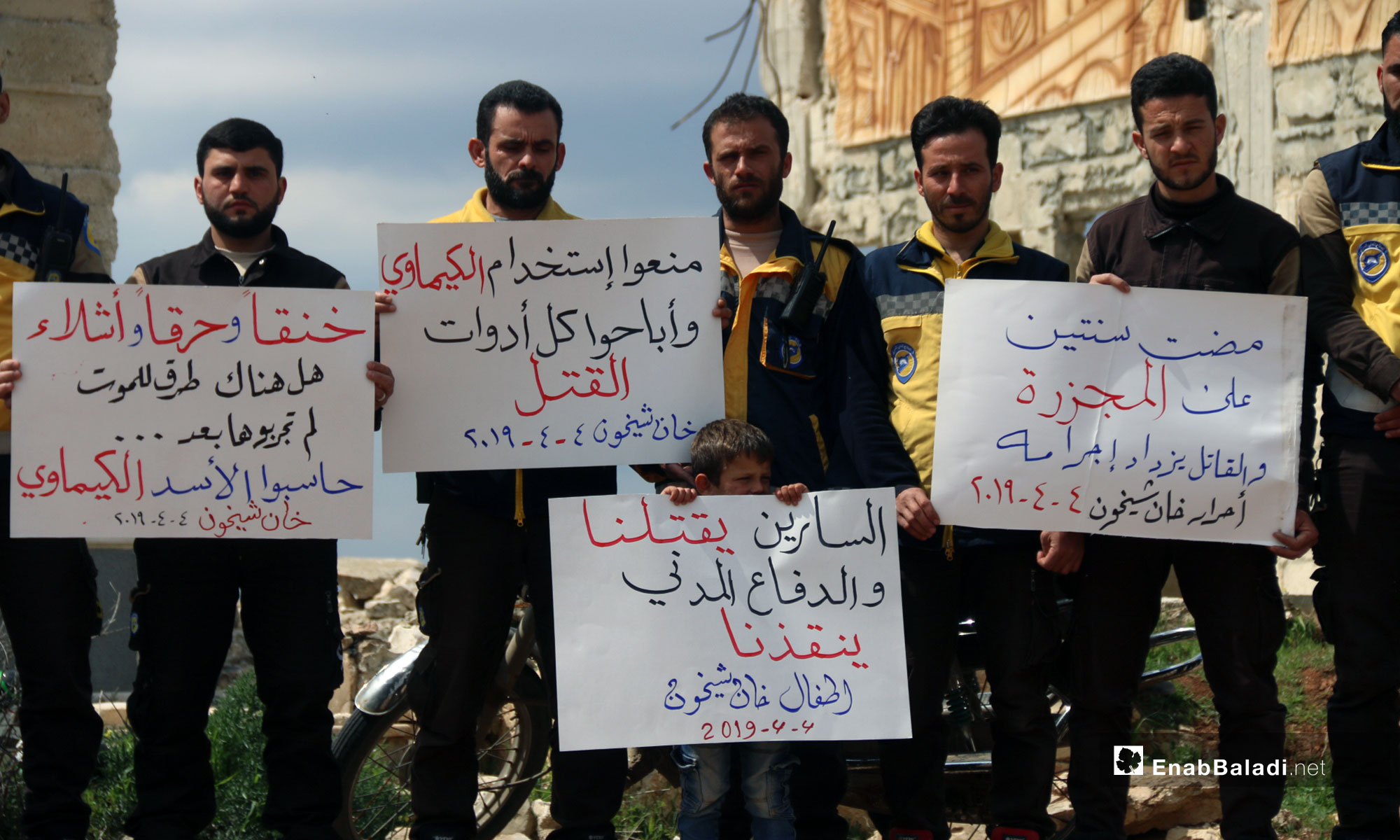 "The signs held by the people say: ""Suffocated, burnt and mutilated, are there any death methods left that you have not tried yet; hold al-Assad accountable, chemical weapons Khan Shaykhun/ Two years have passed since the massacre and the killer's criminality is increasing/They prohibited the usage of chemical weapons and made all the killing tools available/ Sarin gas is killing us and the Civil defense is saving us, the children of Khan Shaykhun."""