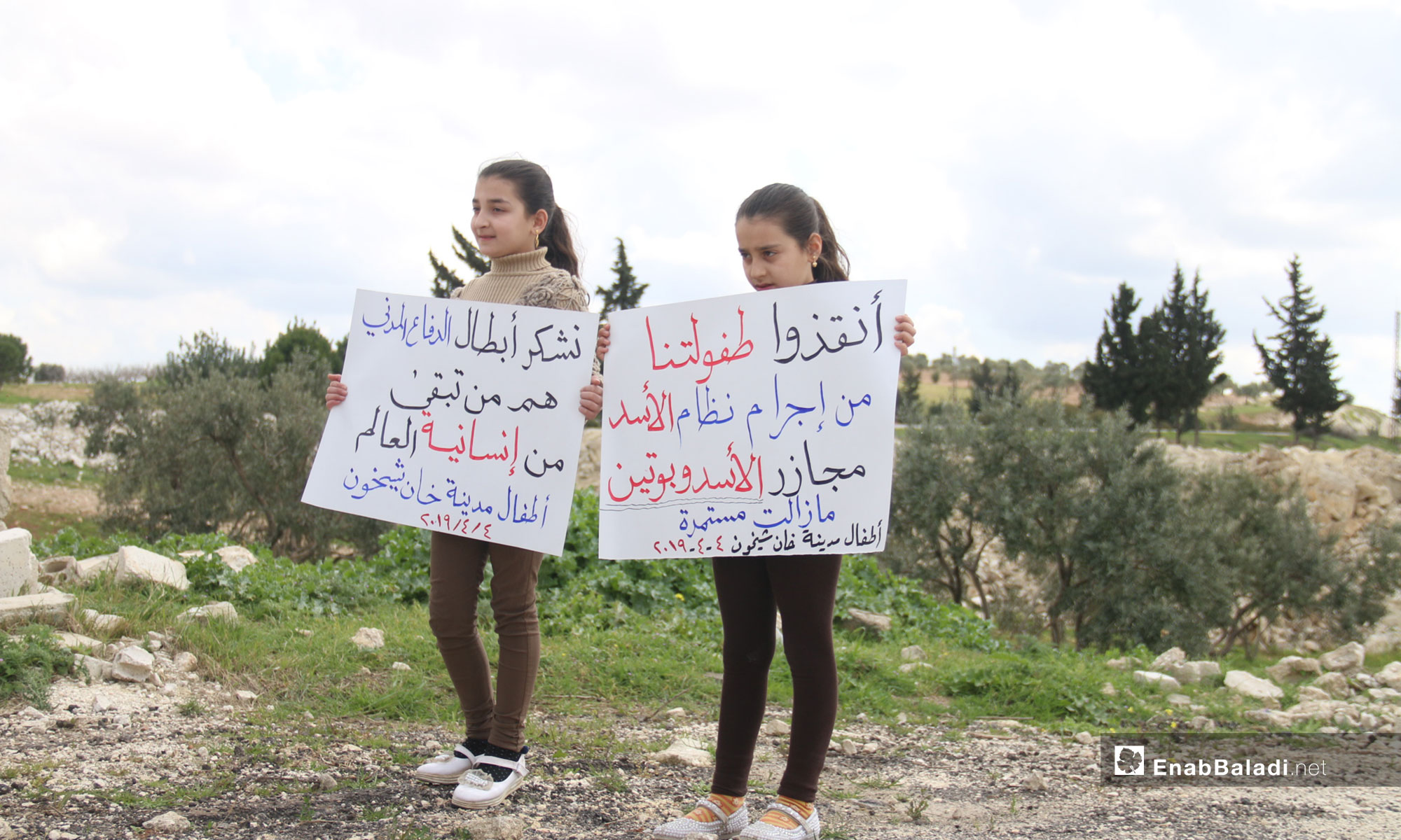 "A vigil at the second anniversary of the chemical massacre of Khan Shaykhun, rural Idlib – April 4, 2019 (Enab Baladi) The signs held by the two little girls say: ""Save our childhood from the criminality of the al-Assad regime; Massacres by al-Assad and Putin are continuing/ We thank the heroes of the Civil Defense, they are what is left of the world's humanity, the children of the city of Khan Shaykhun."""