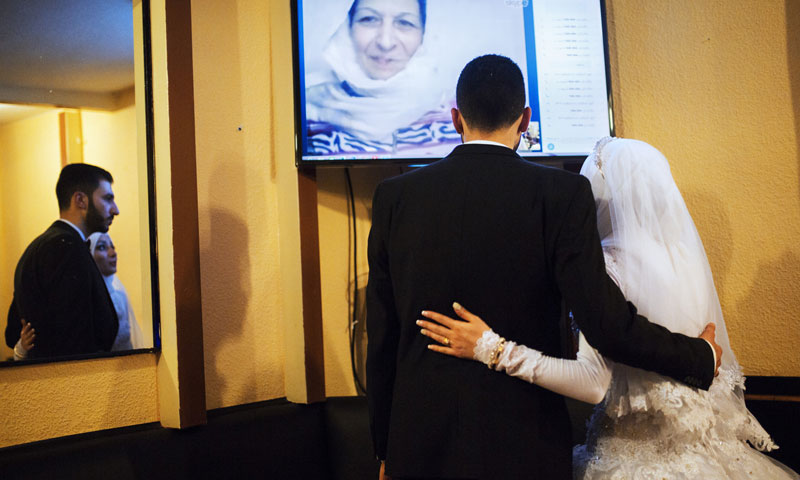 The bride and groom, Salsabeel and Bilal, on a Skype call with their families in Damascus and Wadi Barada (alessiomam)