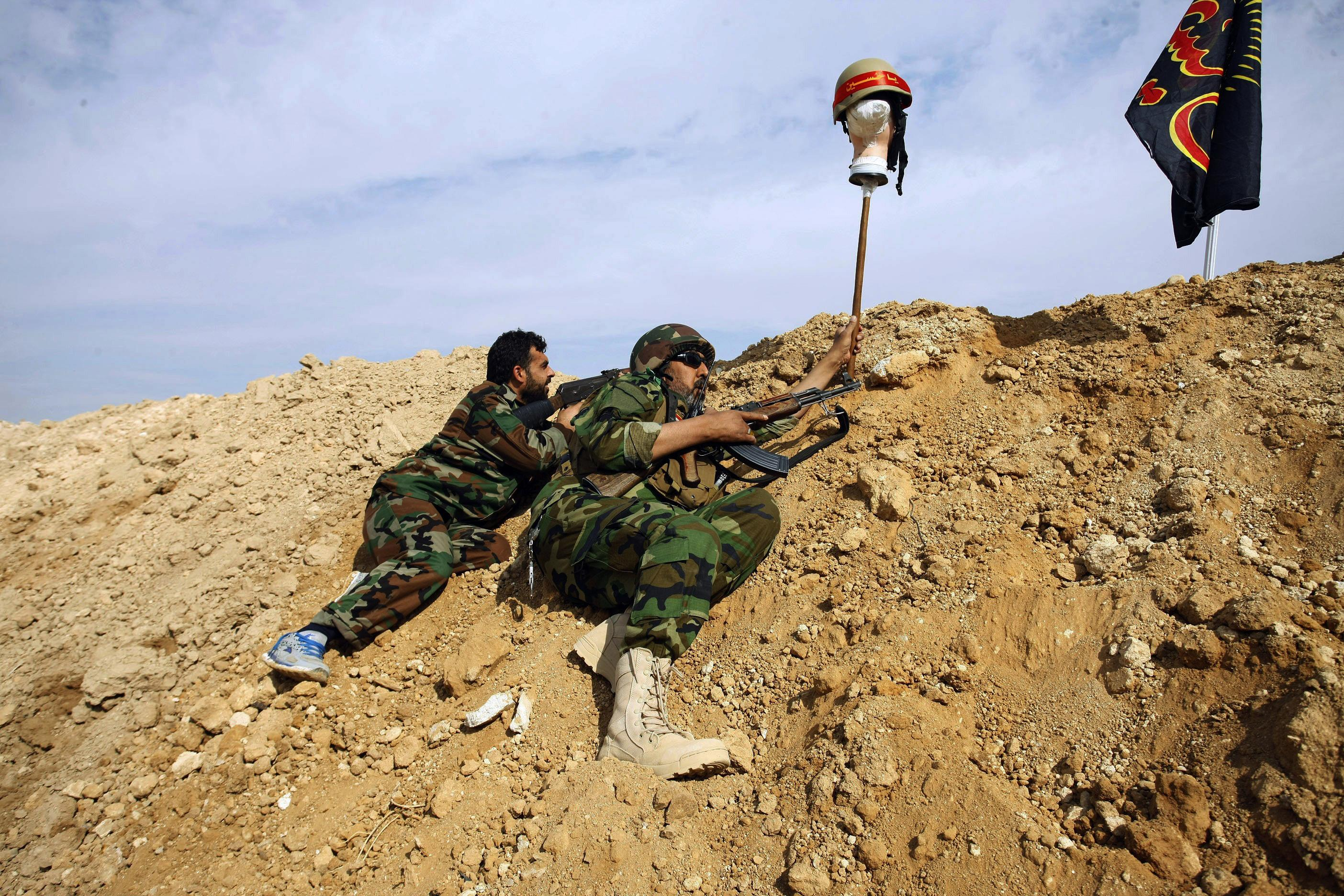 Fighters from the Iranian-backed Hussein Brigade during the battles of El Hajira in Damascus countryside - 2013 (AP)