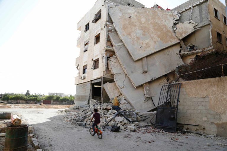 A child riding his bike in Eastern Ghouta next to a building ruined by bombing - September 2017 (SAMAS)