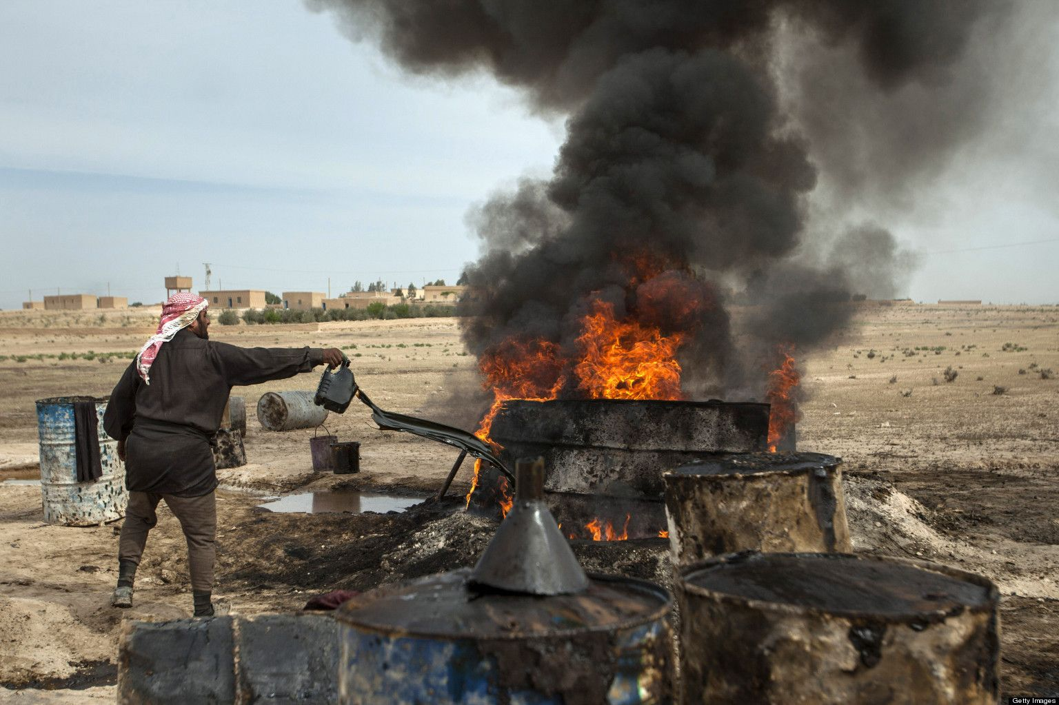 A man in the countryside of Raqqa in front of a pit of petrol - April 15, 2013 (AFP)