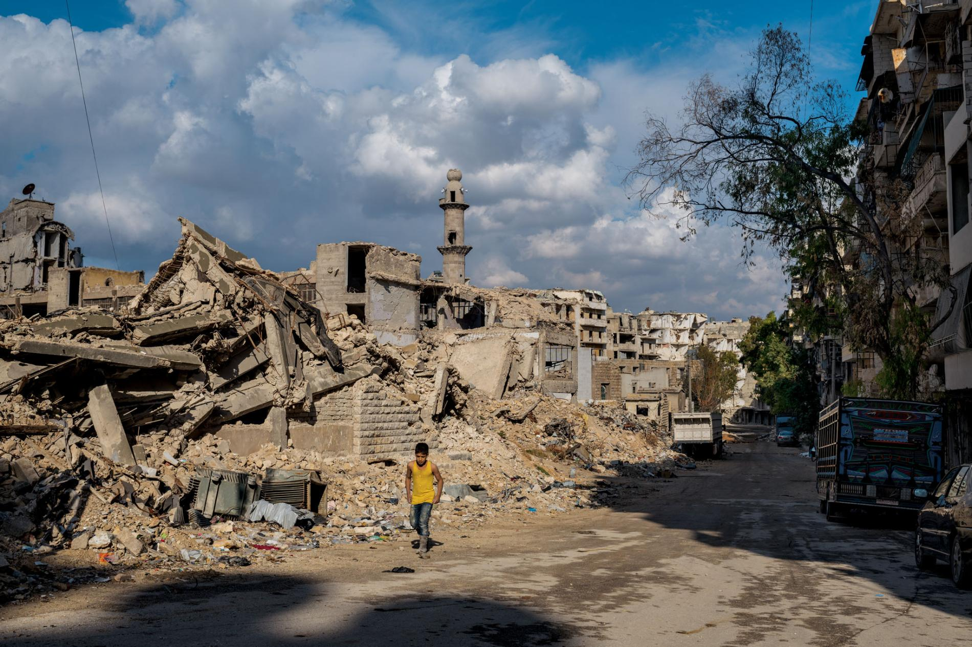 A boy walking in front of a school in Sukkari district south of Aleppo, buildings rubble, February 2019 (National Geographic)