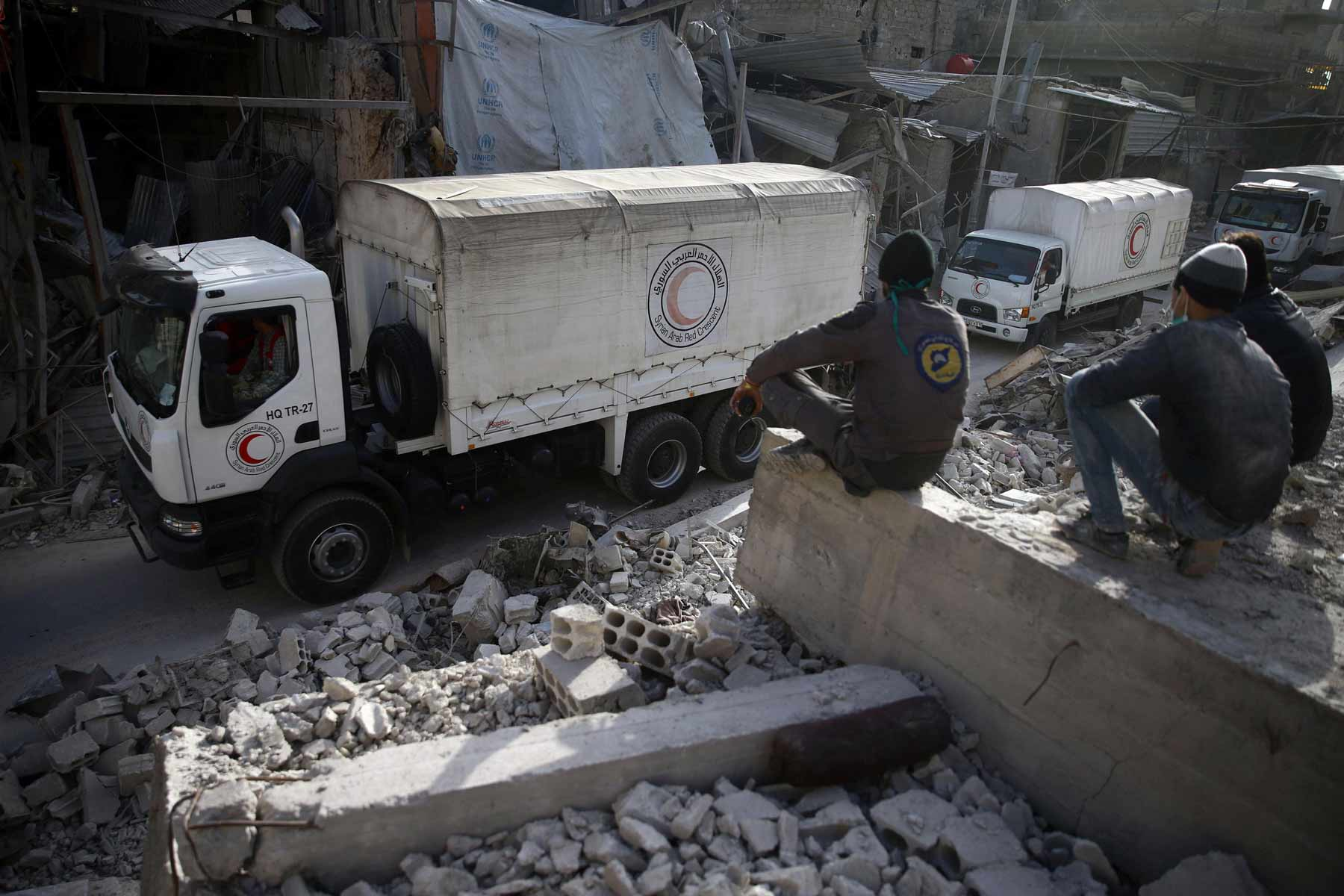 Civil defense volunteers sit on the rubble watching Syrian Red Crescent convoy in besieged Duma - March 2018 (Reuters)