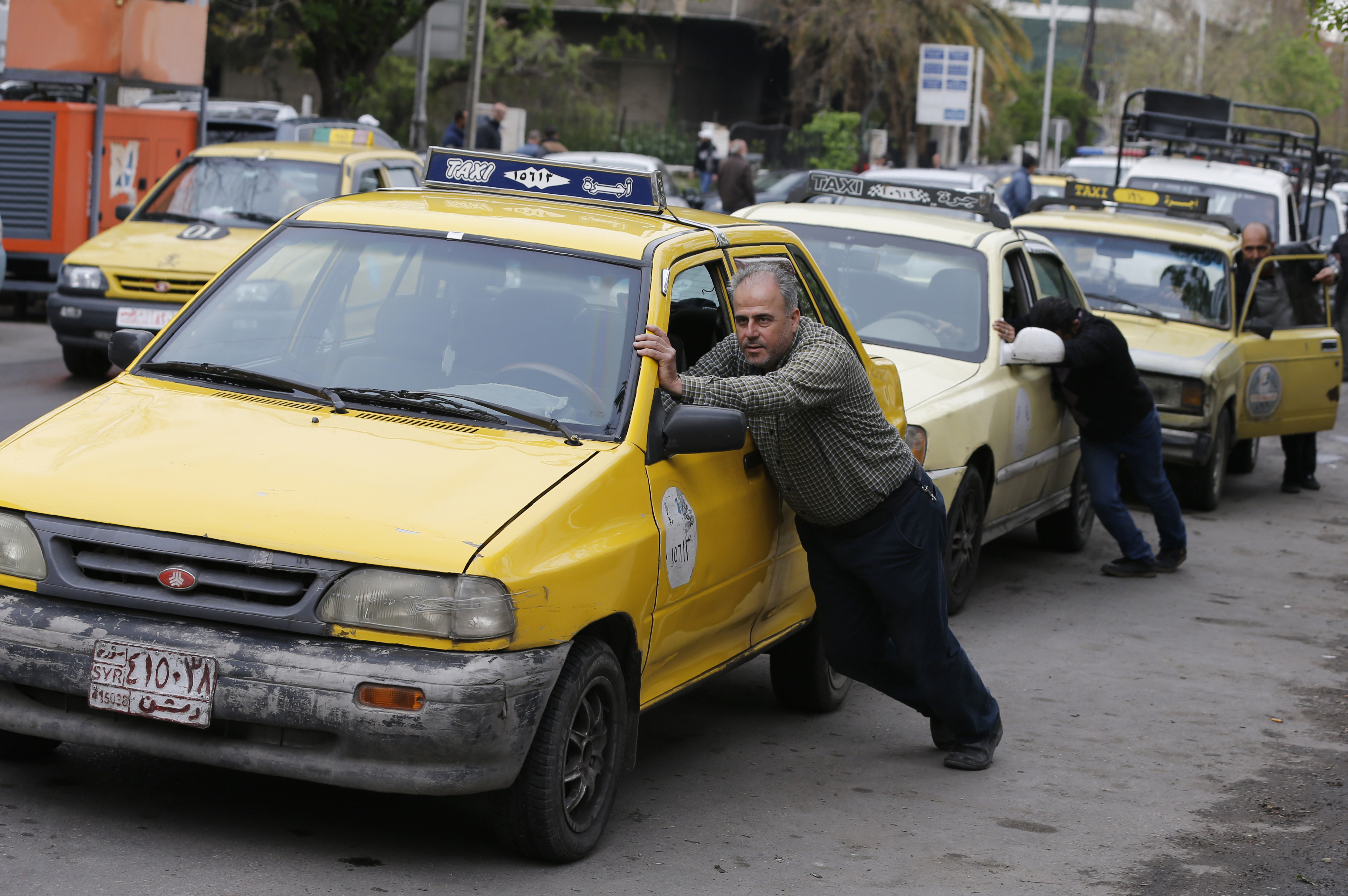 Taxi drivers pushing their cars empty of gasoline to a fuel station in the Syrian capital DAMASCUS, April 16 (Reuters)