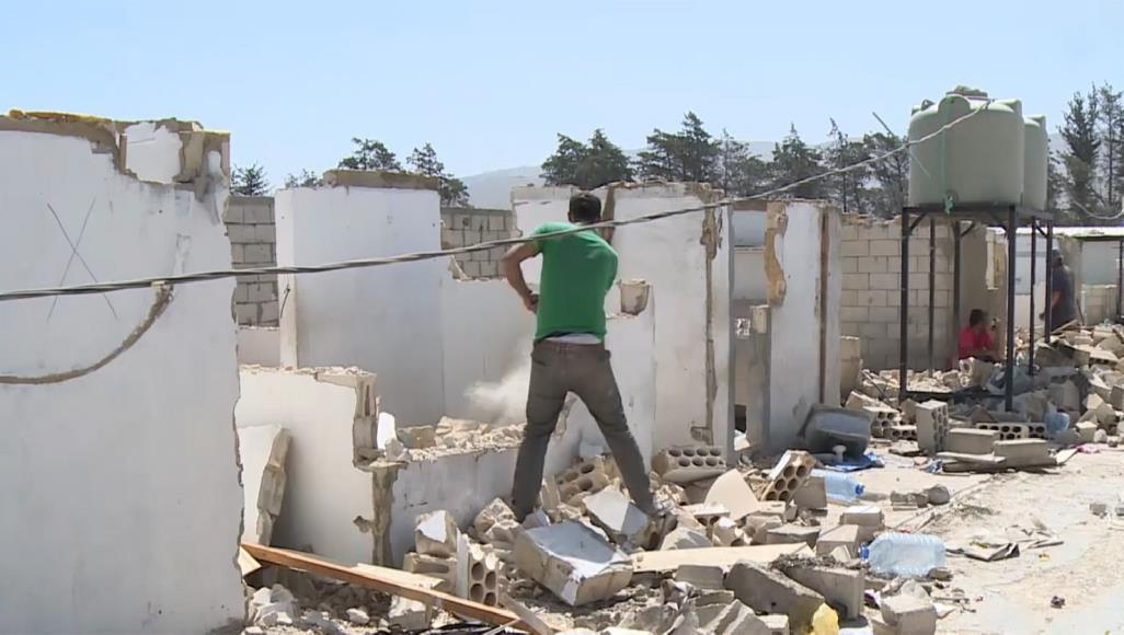 Syrian refugee demolishing his tent in Arsal camp in Lebanon - June 2019 (Al Jazeera)