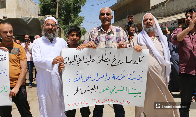 """A demonstration in the city Marea, northern rural Aleppo. The sign carried by the demonstrators says: """"Every Missile Hitting Us on The Fronts, Enhances Our Will and Determination That Our Legal Army Is The Free Army"""" – June 7, 2019 (Enab Baladi)"""