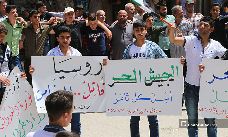 """A demonstration in the city Marea, northern rural Aleppo. The signs carried by the demonstrators say: """"Free Army, the Hope of Every Revolutionary/ Russia, A Murderer, Not a Guarantor"""" – June 7, 2019 (Enab Baladi)"""