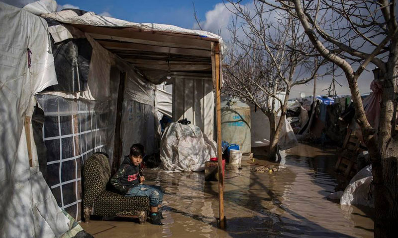A Syrian child refugee sitting in front of his family's tent, which water has drowned in the al-Dalhamiyya Camp, eastern Lebanon – January 15, 2019 (UNHCR)