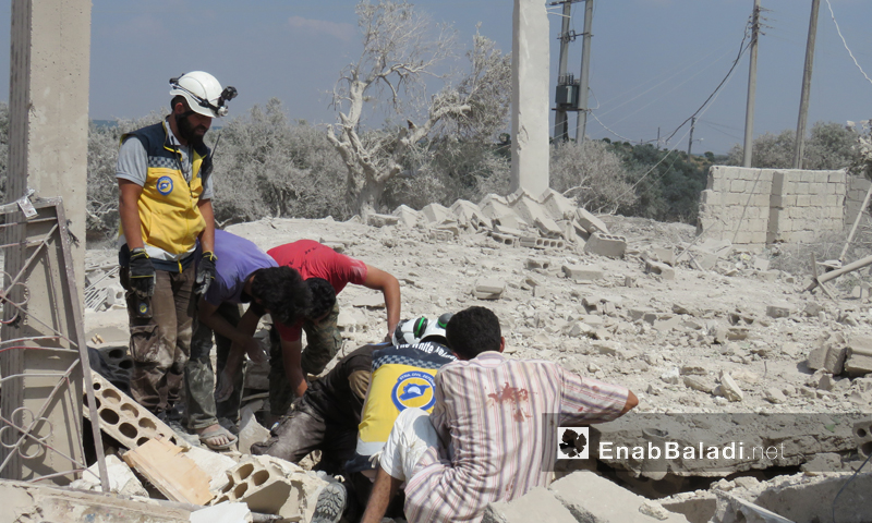 Personnel of the Syrian Civil Defense (White Helmets) evacuating the people affected by the bombing that targeted the town of Fatterah, southern Idlib – June 15, 2019 (Enab Baladi)
