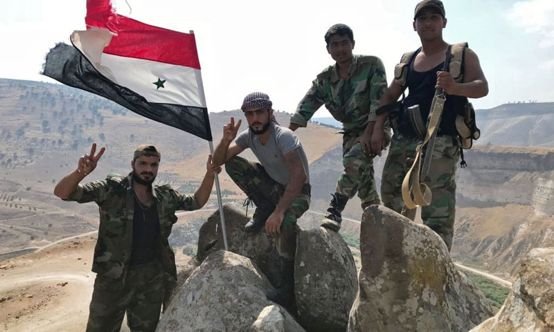 Assad forces' personnel raising the regime's flag in southern Syria, near the borders with Jordan – 2018 (Sputnik)