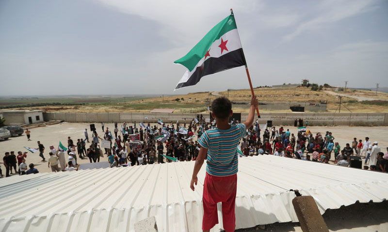 A child raising the flag of the Free Syrian Army (FSA) during a protest calling for stopping the shelling and for Turkey to open the borders – May 31, 2019 (Reuters)