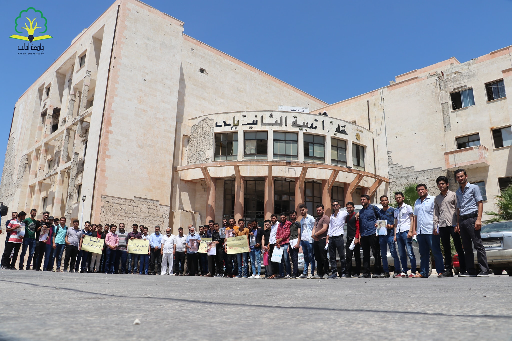 Students and staff of the Faculty of Education at the University of Idlib standing in honor of one of the martyred students (University's Facebook page)