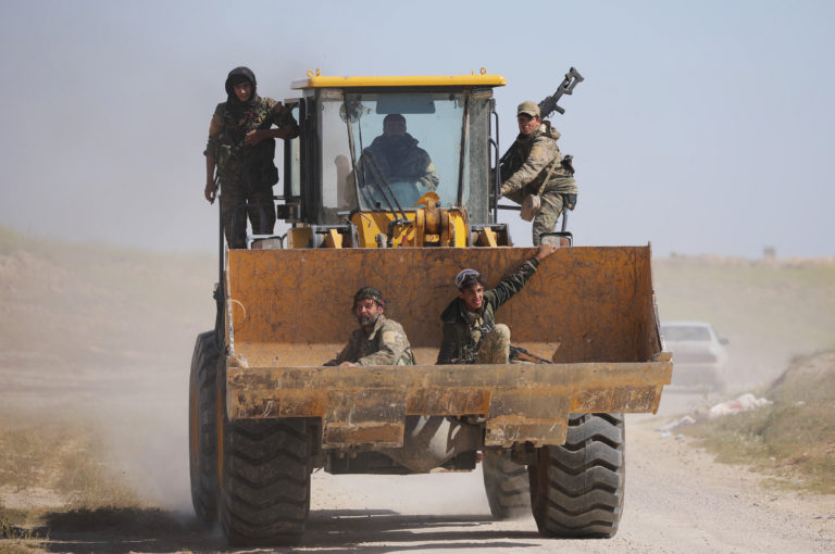 Fighters sitting inside the bucket of a bulldozer at al-Baghouz village in the countryside of Deir ez-Zor - March 2019 (Reuters)