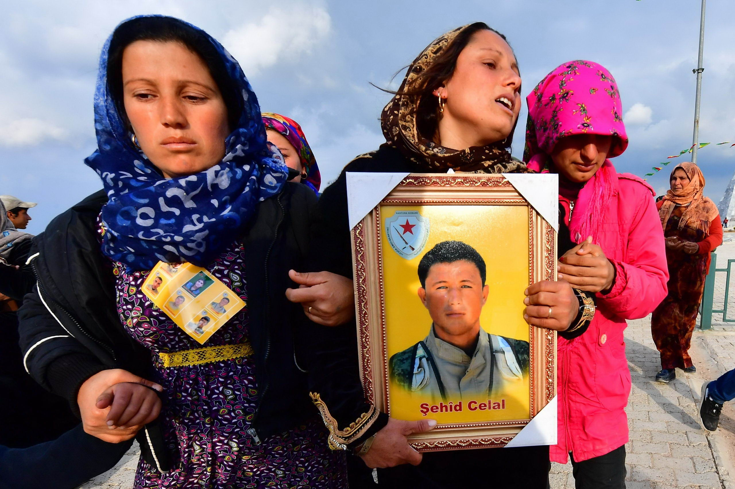Relatives of an SDF fighter holding his photo at his funeral in Manbij, east of Aleppo - 2019 (AFP)