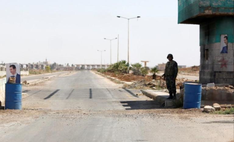 A Syrian soldier standing at Nasib crossing bordering Jordan in Daraa on July 7, 2019 (Reuters)