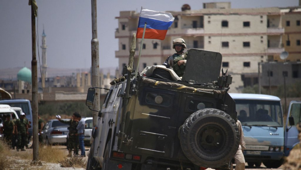 A Russian soldier riding an armored vehicle and watching opponents to the settlement agreement during their evacuation from the city of Daraa - 15 July, 2018 (AFP)