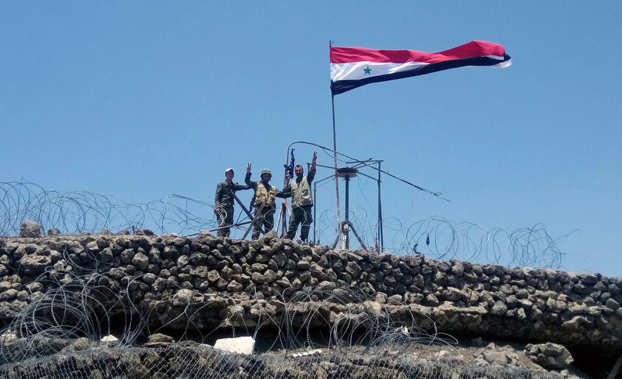 Regime forces soldiers raising victory sign next to the flag in Tall al-Harrah on the highest hill in the southeastern governorate of Daraa (AFP)