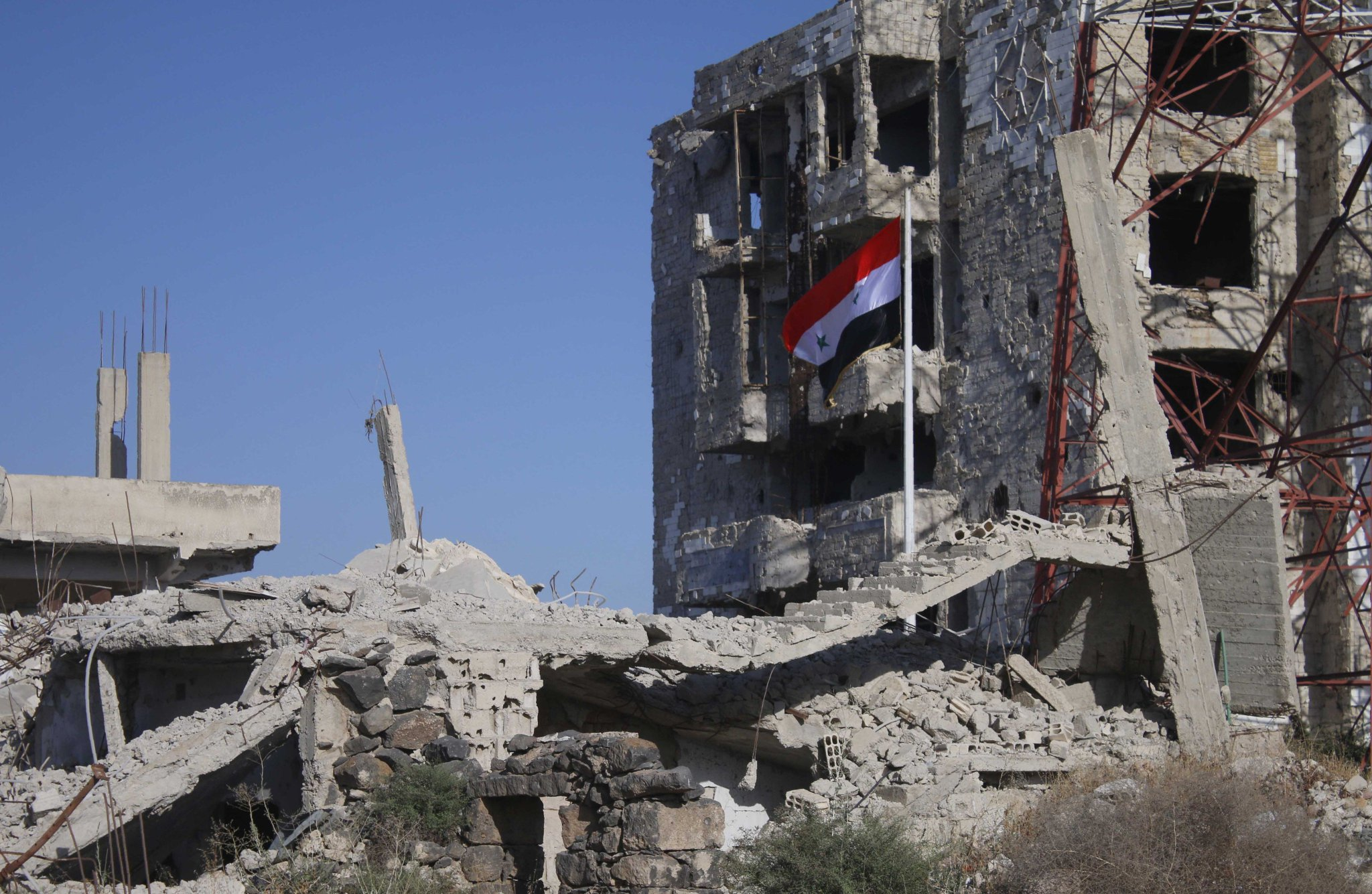 The flag of the Syrian regime on top of the ruins of the buildings in the city of Daraa - 12 July, 2018 (AFP)